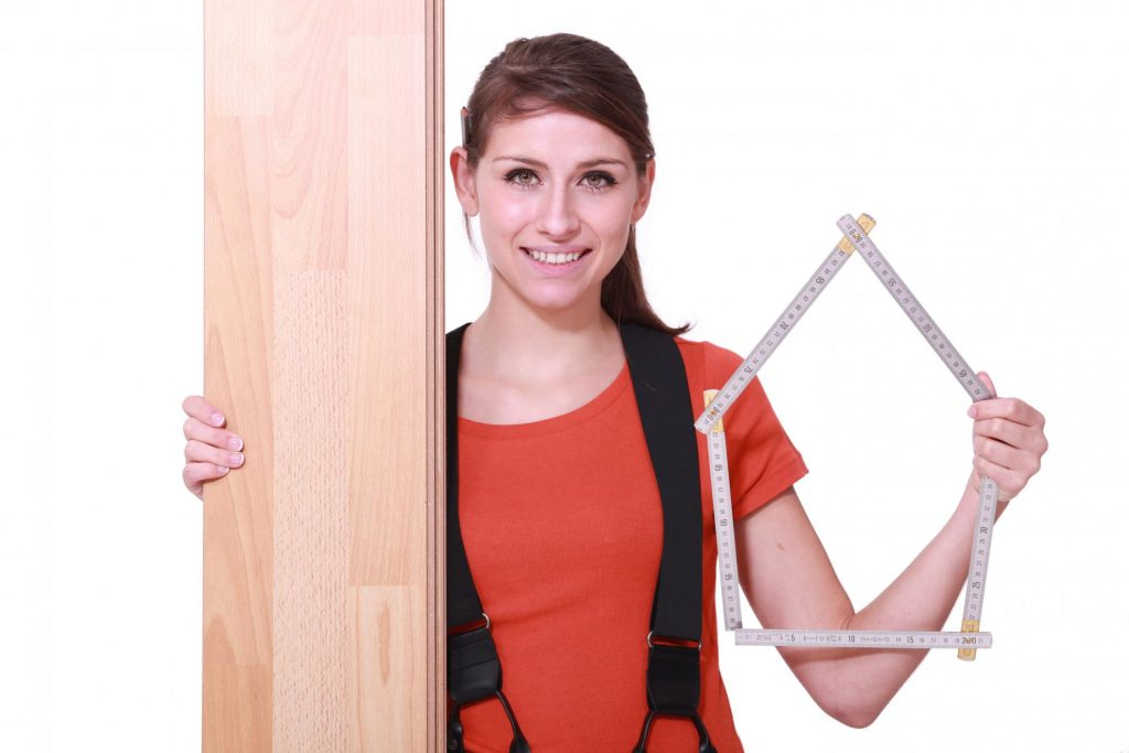 a lady holding a measuring tool and a plywood